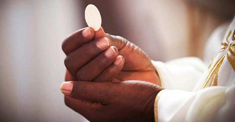 sagrada hostia sostenida en las manos de sacerdotes para comunion