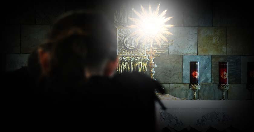 santisimo iluminado luz irradia de la hostia consagrada altar orando