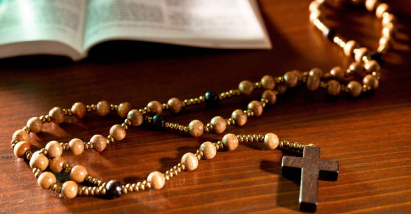 santo rosario de madera marron puesto sobre mesa y biblia