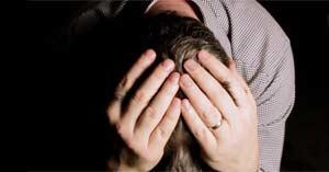 hombre manos en la cabeza atormentado fondo negro