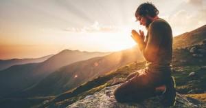 hombre orando montana atardecer de rodillas