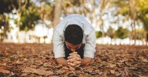 hombre rezando arrodillado sobre hojas caidas de un arbol