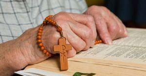 hombre rosario en mano orando con biblia