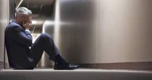 hombre sentado piso pasillo deprimido triste