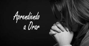 mujer con manos juntas orando en oracion fondo negro aprendiendo a orar