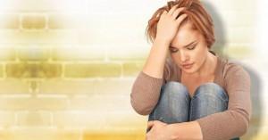 mujer preocupada angustiada sentada con la mano en la cabeza