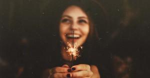 mujer sonriendo con fuego artificial encendido entre sus manos
