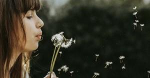 mujer soplando una flor en el bosque fondo arboles oscuros
