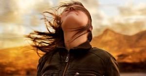 mujer viendo hacia el cielo viento en sus cabellos fondo montanas