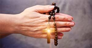 rosario de madera en mano orando