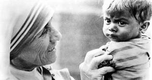 santa teresa de calcuta sonriendo sostiene un nino entre sus manos blanco y negro