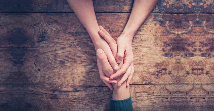dos manos de mujer sosteniendo la mano de un hombre sobre una mesa de madera