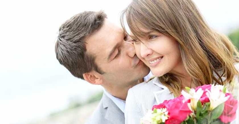 esposa besando a su esposa sonriendo con flores matrimonio saludable