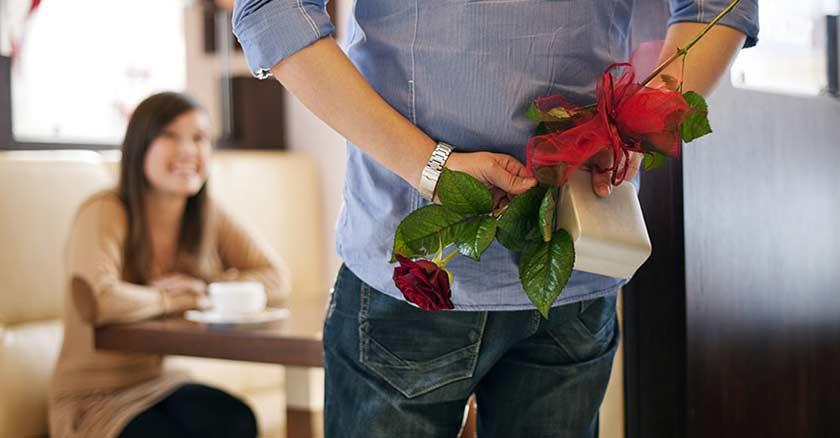 esposo con regalo sorpresa y flores en su espalda sorprende a su esposa novia amor