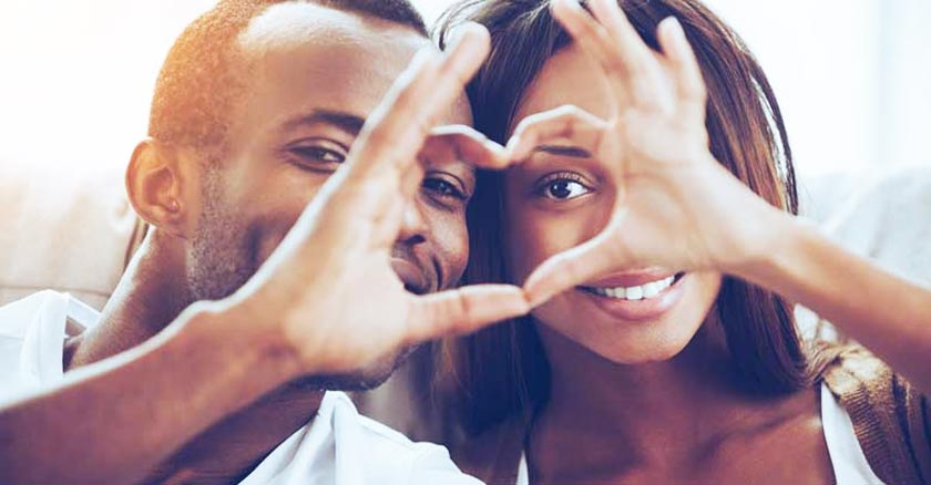 esposos felices formando un corazon con sus manos juntas dia