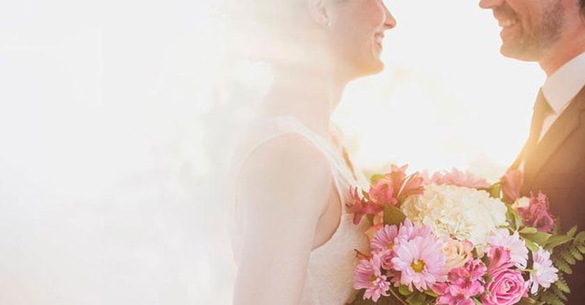 esposos-felices-recien-casados-boda-matrimonio-sostienen-buquet-de-flores-luz-blanca.jpg