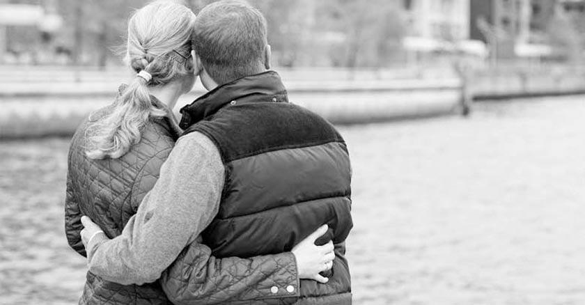 esposos juntos abrazados orilla de un rio en ciudad fondo blanco y negro dia
