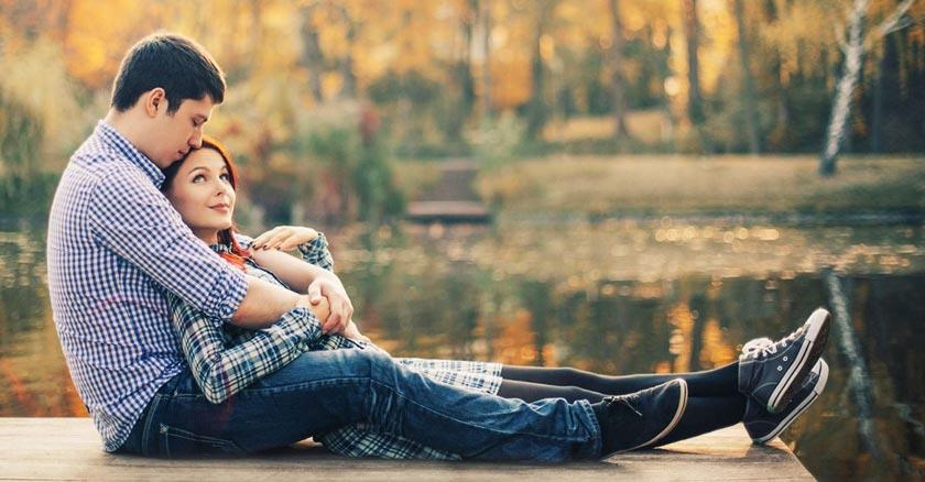esposos juntos sentando en un muelle a orillas de un lago dia