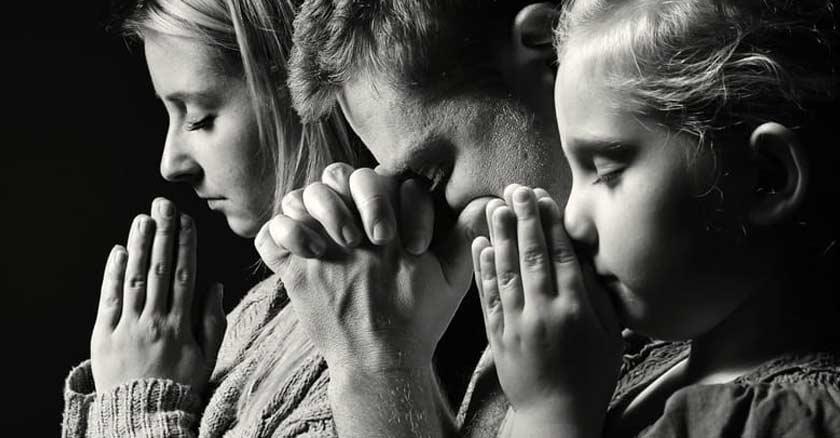 familia unida en oracion orando papa mama hija fondo negro bamclo y negro