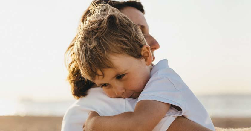 hijo cargado en sus brazos por su mama fondo playa arena