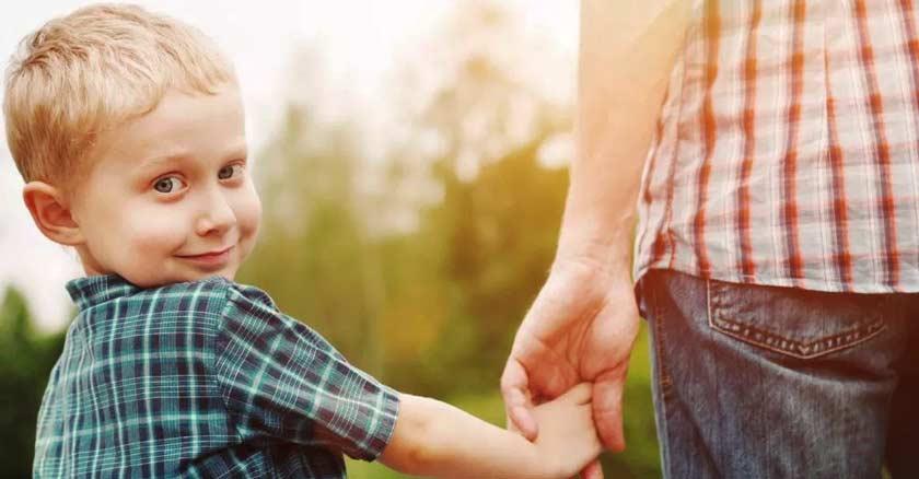 hijo sonriendo tomado de la mano de su papa mirando hacia la camara