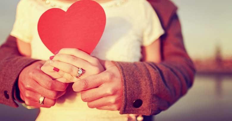 hombre abraza mujer sostiene corazon rojo en sus manos