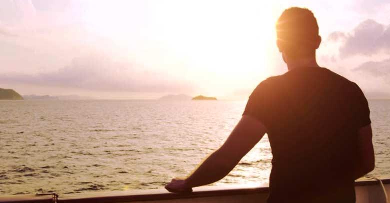 hombre de espalda mirando el mar ocaso sol