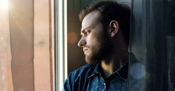 hombre mirando triste ventana esposo