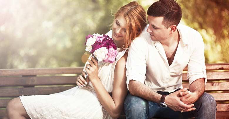 hombre mujer sentados banco de parque ramo de flores