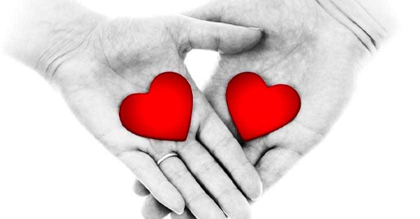 mano de hombre y mujer sosteniendo corazon corazones rojos fondo blanco