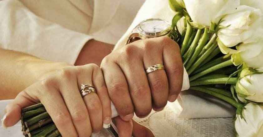 manos de esposa esposo sosteniendo un buquet con anillos de matrimonio en sus dedos
