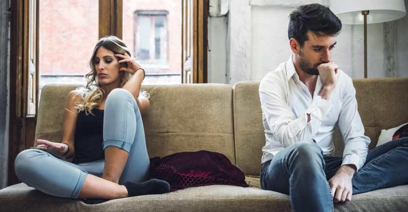 matrimonio hombre y mujer sentados separados en un sofa moelstos tristes apatia