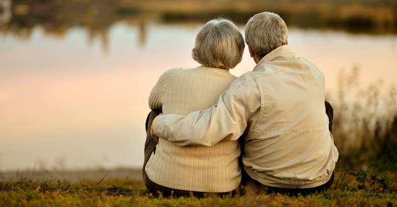 matrimonio pareja feliz observando lago ocaso