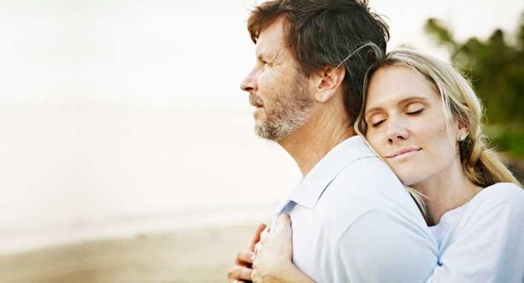 mujer abraza esposo mirando playa matrimonio