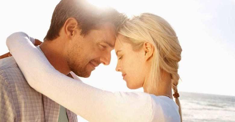 mujer abrazando a su pareja hombre muelle playa sol