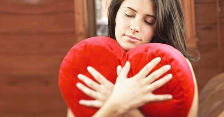 mujer abrazando almohada con forma de corazon rojo amor