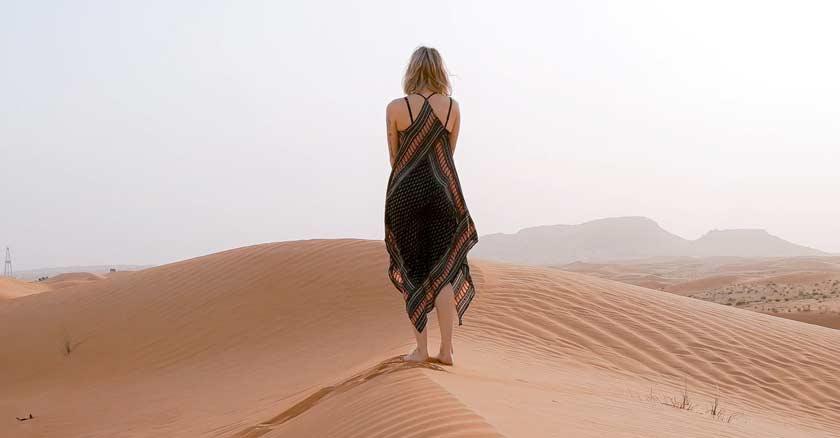 mujer caminando sola por desierto solitaria soleado