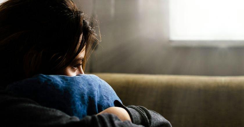 mujer deprimida sentada en un sofa solitaria triste luz por la ventana
