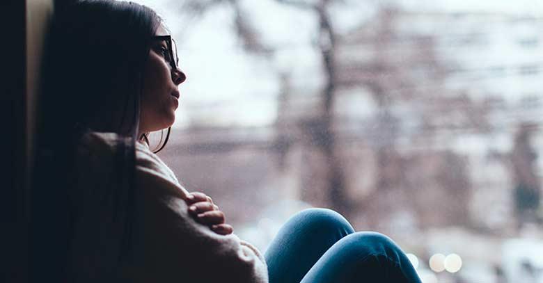 mujer recostada ventada con tristeza corazon roto
