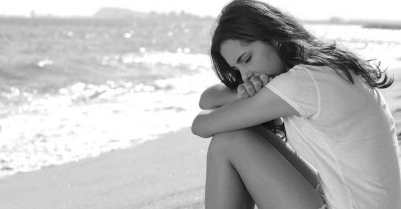 mujer sentada a la orilla de la playa triste