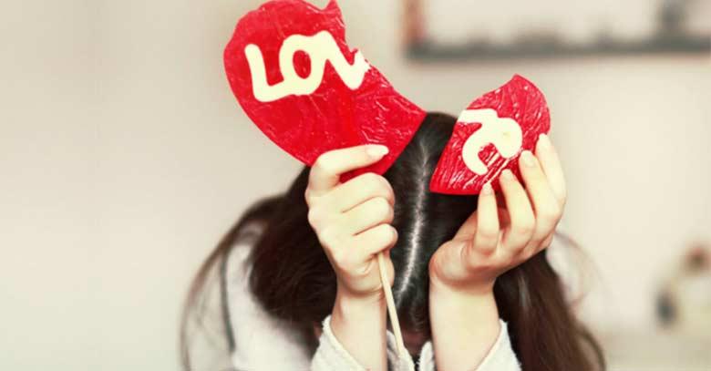mujer sostiene un corazon rojo roto triste infidelidad matrimonio