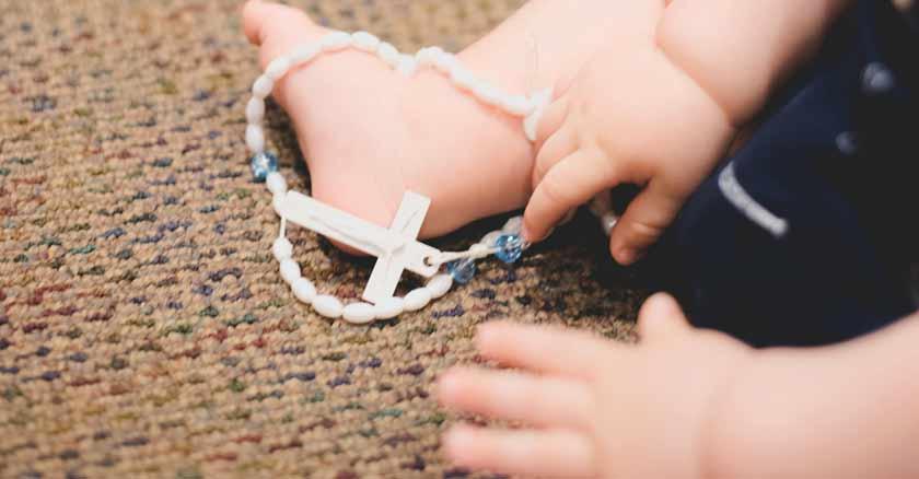 nino con rosario en mano educar hijos santos en este mundo