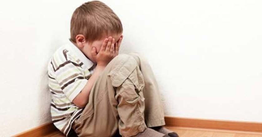 nino sentado en un rincon de la casa llorando con las manos cubriendo su rostro
