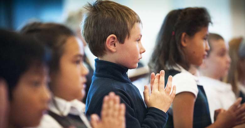ninos en la santa misa rezando manos juntas