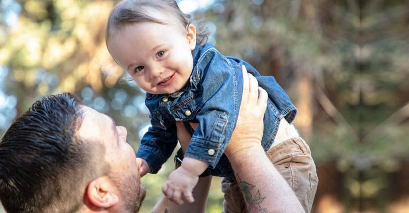 padre levantando a su hijo bebe mientras este sonrie