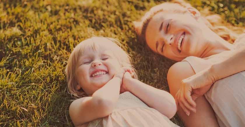 palabras motivadoras para hijos mama y su hija bebe sonriendo recostadas sobre cesped