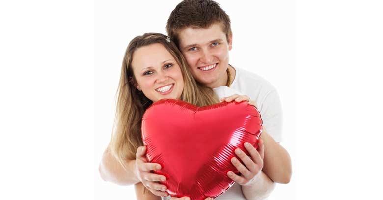 pareja de esposos felices abrazados sotienen corazon rojo
