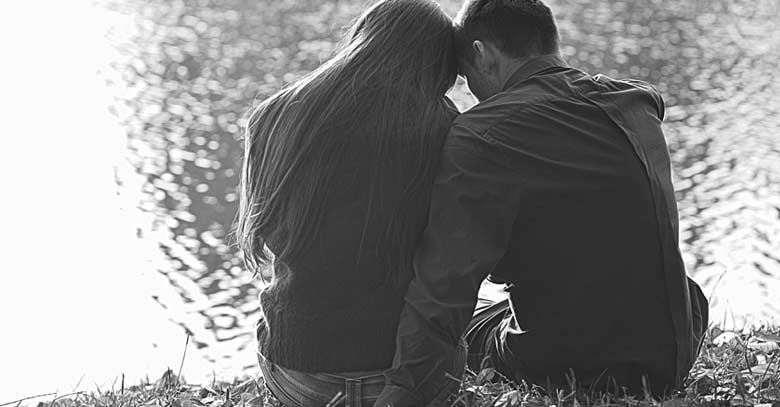 pareja de esposos sentado a la orilla de un lago