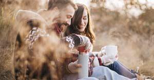 esposos sentados en el campo tomando cafe sonriendo felices matrimonio