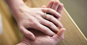 manos de esposos juntas sobre una mesa anillo de matrimonio dia